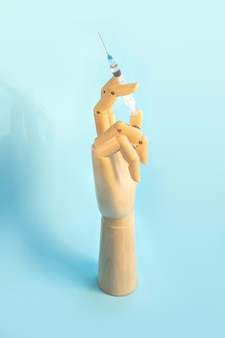 のためのワクチンと注射器と木製の人間の手