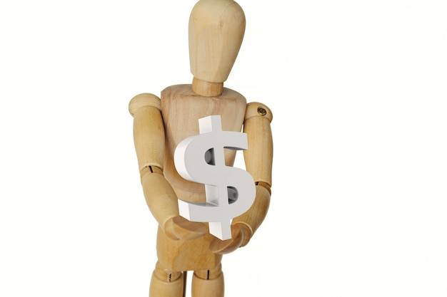 Wooden human mannequin holding dollar sign.