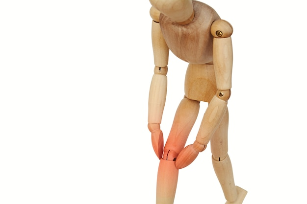 Wooden human with knee pain.