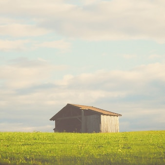 Wooden hut on the field with retro filter effect