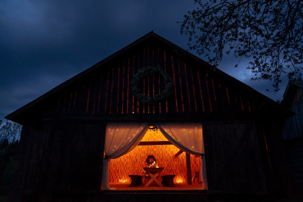 Wooden hut with table set inside lit by candles creating cozy atmosphere ready for a weeding banquet