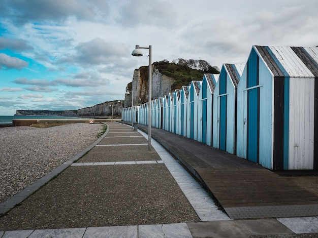 木造の小屋イポールノルマンディーフランスの小石のビーチにある青と黒のビーチ小屋