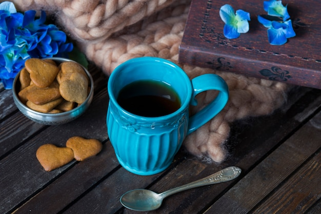 On a wooden hydrangea table, a blanket, a book, a blue tea mug and biscuits
