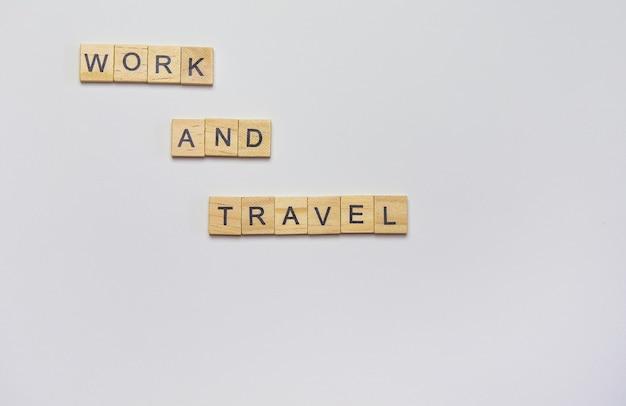 立方体からの木製の碑文-白い壁、上面図で仕事と旅行。