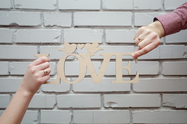 Wooden inscription love on white brick background close up. couple in love hold wooden sign