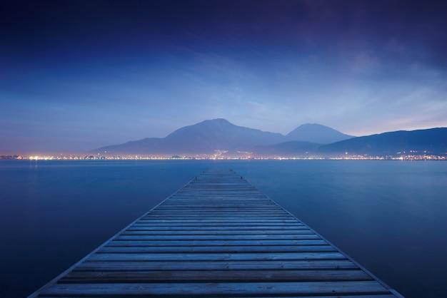 海の夕日と空の反射水に木製の桟橋。長期露出。