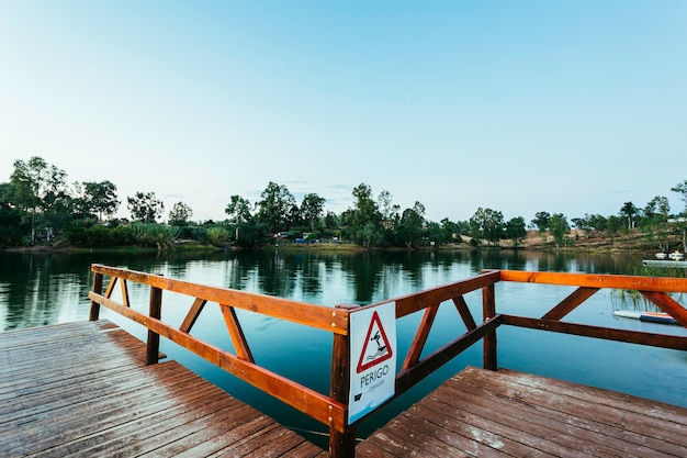 Wooden jetty with danger sign jumping into the water