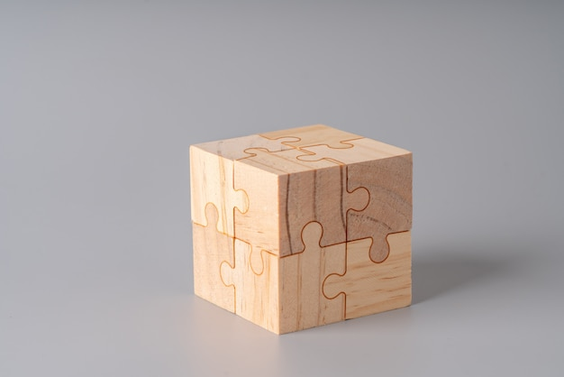 Wooden jigsaw puzzle cube on gray background