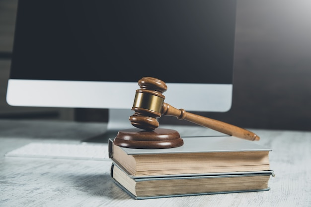 Wooden judge on book on computer background