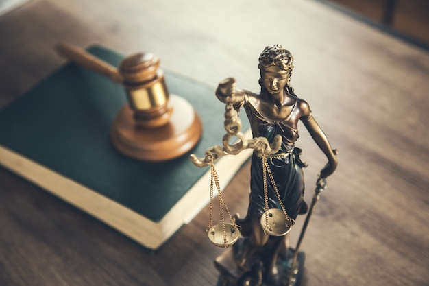 Wooden judge on book with justice lady on desk