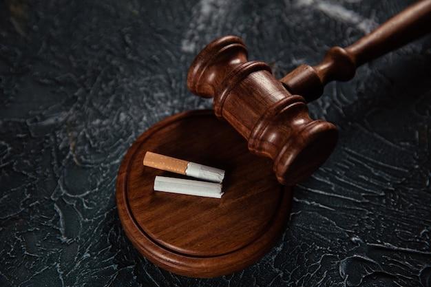 灰色の表面に木製の裁判官小槌と壊れたタバコ。たばこ法