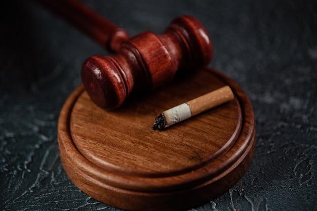 灰色のテーブルに木製の裁判官小槌とタバコ。たばこ法の概念