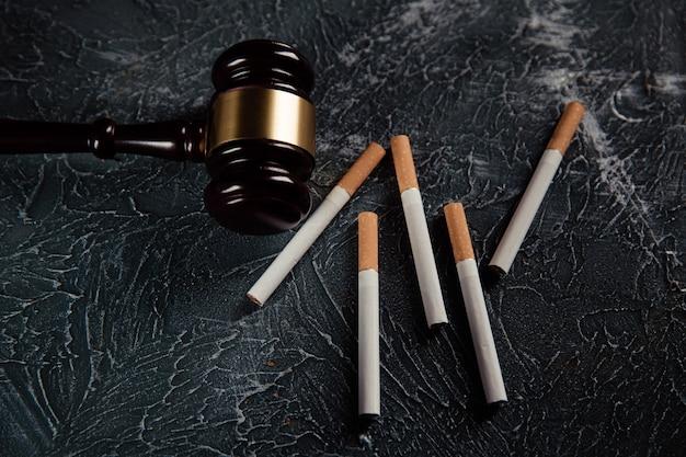 木製の裁判官小槌と灰色のテーブルに5本のタバコ。たばこ法