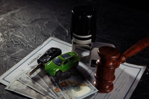 Деревянный молоток судьи и зеленая игрушечная машинка с ключами. символ закона, справедливости и автомобильного аукциона.