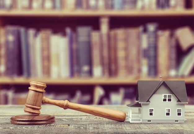 Деревянный молоток судьи и игрушечный домик на фоне