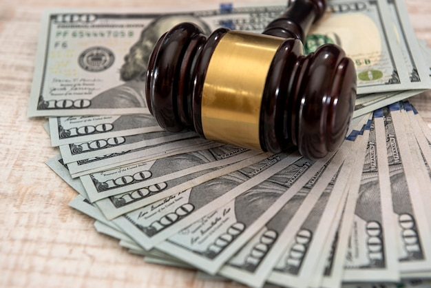 Деревянный молоток судьи и долларовые банкноты сша. концепция взятки