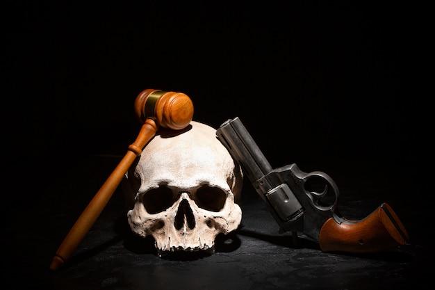 Wooden judge gavel hammer on human skull with revolver gun pistol