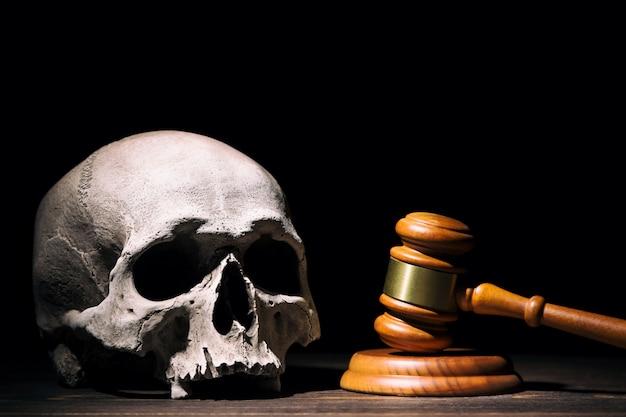 Wooden judge gavel hammer near human skull against black background.
