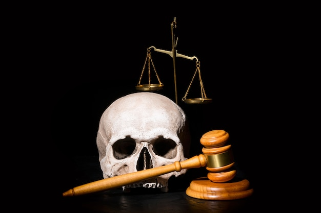 Wooden judge gavel hammer near human skull and brass scales