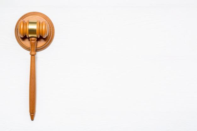 Wooden judge gavel hammer on white wooden table background.