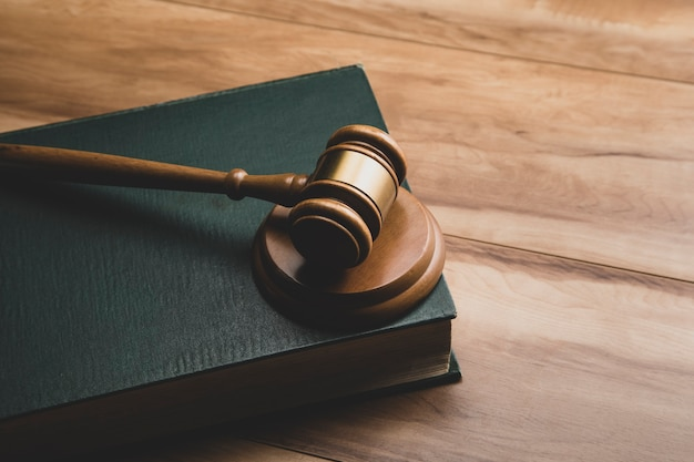 Wooden judge gavel and legal book on wooden table