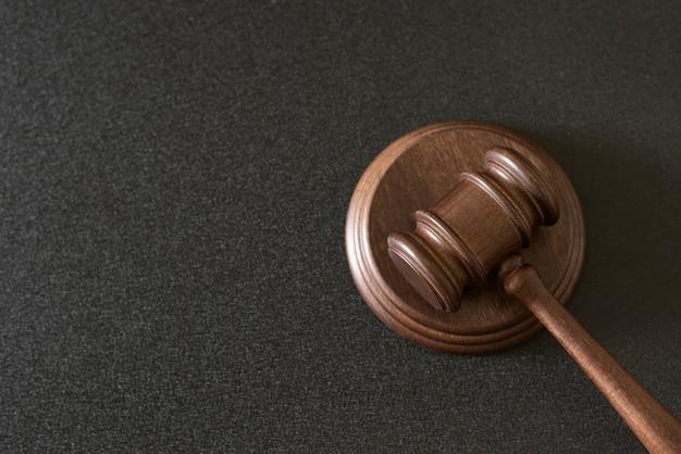 Деревянный молоток судьи на черном фоне. скопируйте место для текста. судебный иск.