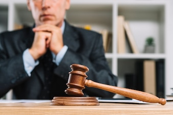 Wooden judge gavel on table in front of lawyer