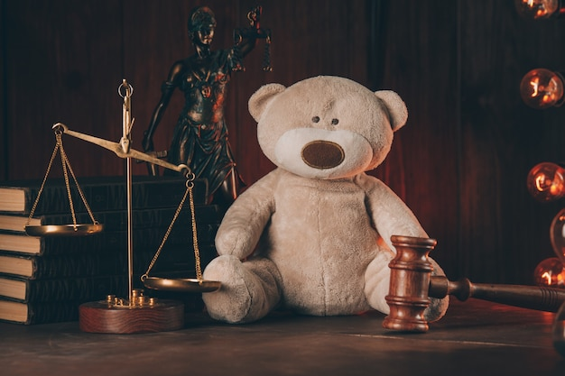 Wooden judge gavel and teddy bear in notary public office