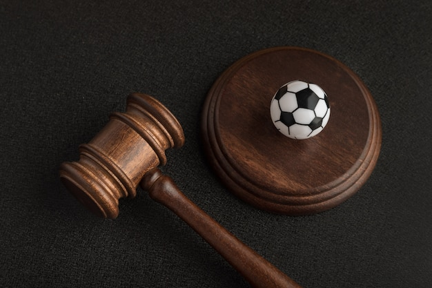 Wooden judge gavel and toy soccer ball. football coach accused. concussion lawsuit.