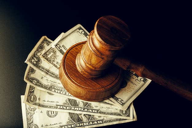 Wooden judge gavel on us dollar banknotes closeup. justice corruption concept