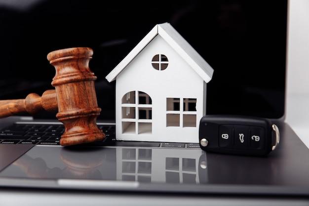 Деревянный молоток судьи с домом и ключом от машины на ноутбуке. интернет-аукцион или концепция торгов.