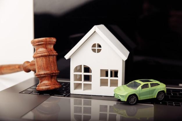 家と車を備えた木製の裁判官の小槌。