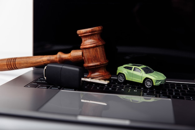 Wooden judge gavel with key and car auction and bidding concept