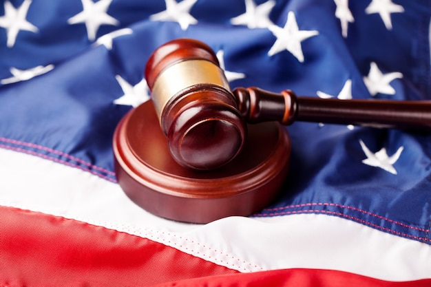 Wooden judge hammer on american flag background. justice and law concept