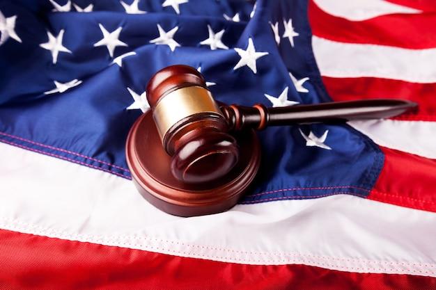 アメリカの国旗の背景に木製の裁判官ハンマー。正義と法の概念