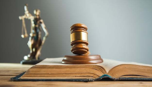 Деревянный судья по книге с леди правосудия на столе