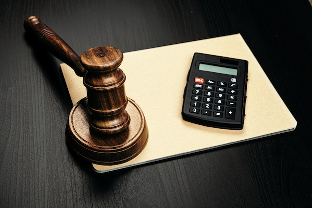 Wooden judge's gavel and calculator on table