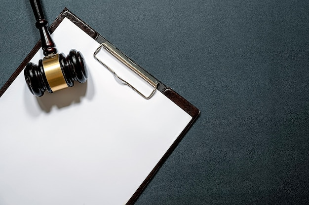 Wooden judge's gavel and paper clipboard on black leather background.
