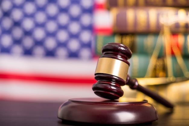 木製の裁判官ガベル、黒の背景を持つ黄金の鱗の正義