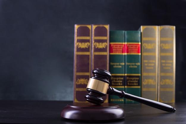 木製の裁判官のガベル、黒の背景を持つ黄金の鱗の正義。