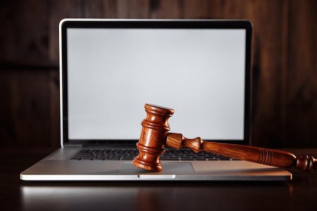 木製の裁判官は、コンピューターのキーボードでガベルをします。サイバー法と犯罪インターネットの概念。