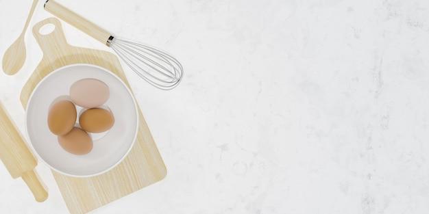 내부와 흰색 대리석 표면에 계란 그릇이있는 나무 주방 액세서리