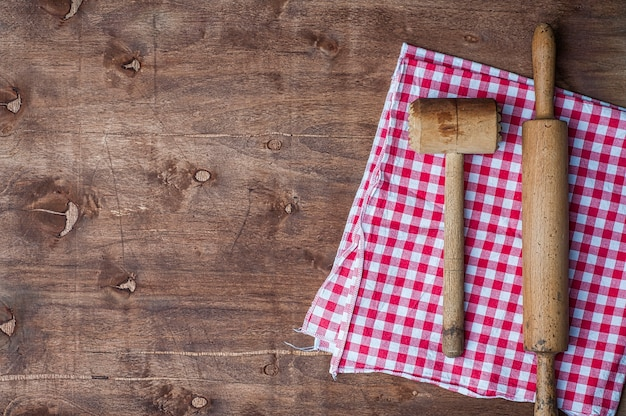 Wooden kitchen items on a red napkin, rolling pin and hammer for beating meat
