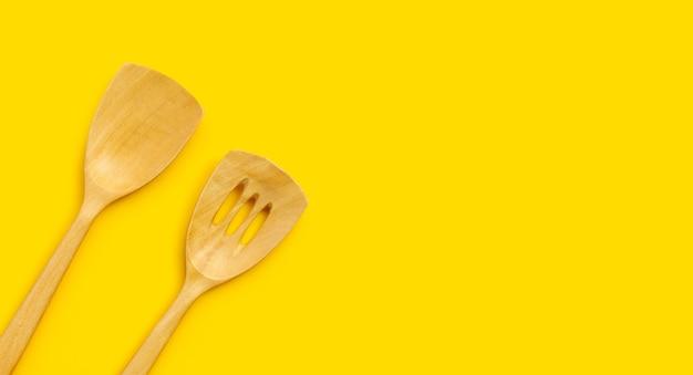 Деревянный кухонный шпатель на желтом фоне.