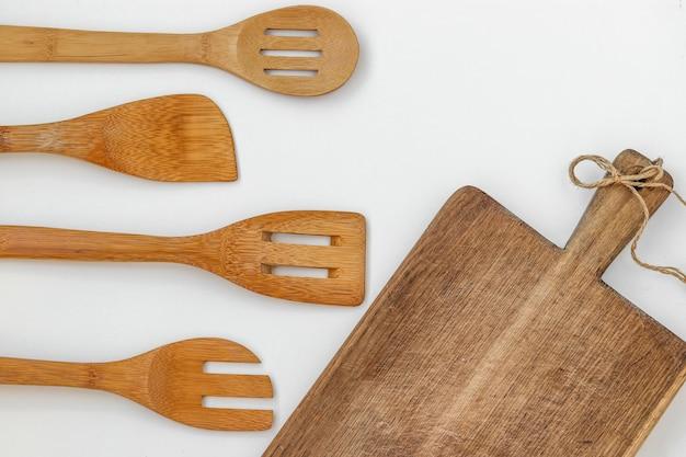 Wooden kitchen utensils on a white surface, top view, horizontal orientation, closeup