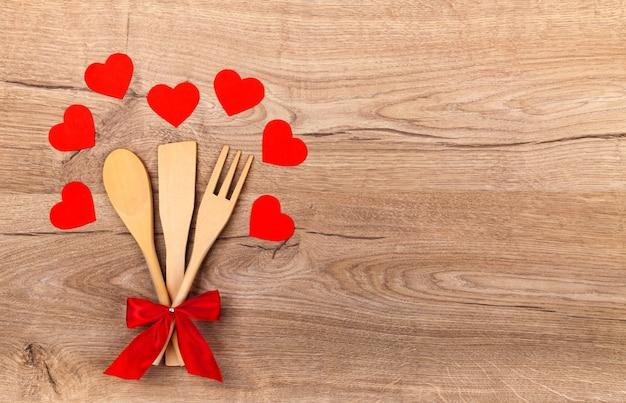 赤い弓、木製の背景に紙の赤いハート、テキスト用の空きスペースが付いた木製の台所用品。調理スプーン、ヘラ、フォーク。バレンタインデーのキッチンの背景。愛を込めて料理する。上面図
