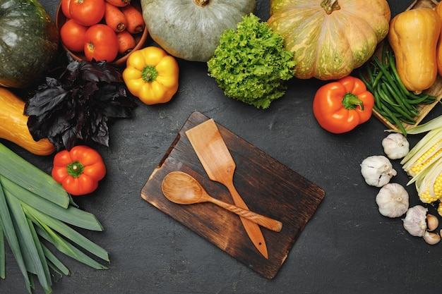 黒の背景の上面図に新鮮な野菜に囲まれた木製の台所用品