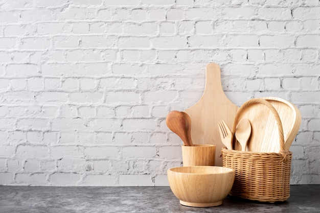 Wooden kitchenware on white brick wall texture background, copy space.