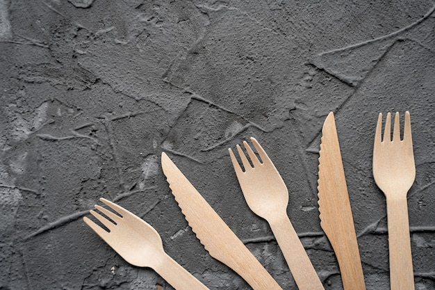나무 칼과 포크 검은 배경입니다. 친환경 제로 폐기물 개념. 텍스트를위한 공간이있는 상위 뷰. 공간 복사
