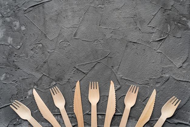 黒の背景に木製のナイフとフォーク。環境にやさしいゼロウェイストコンセプト。テキスト用のスペースがある上面図。コピースペース